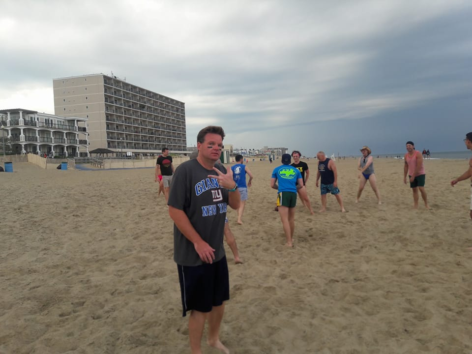 Tim Schlittner plays football on the beach with his friends.